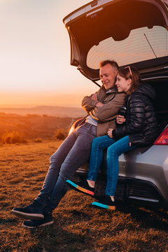 Father and daughter enjoying sunset while sitting in the car trunk