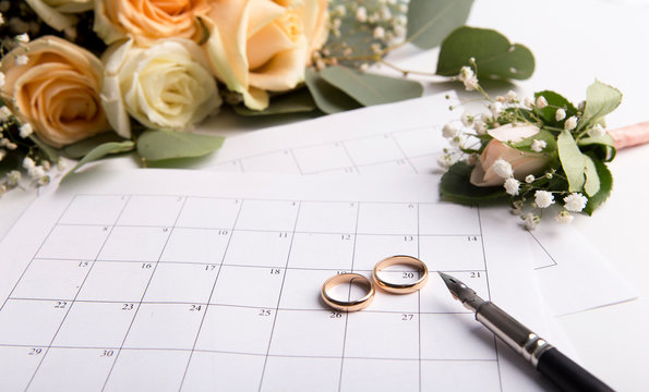 Planning wedding with golden rings on date in calendar