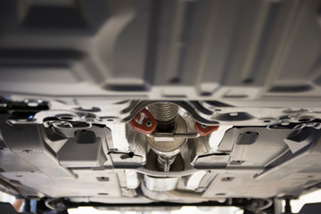 The car is lifted on a lift in a car service. View of the car from below. Focus in the center. Artistic blur.