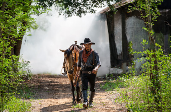 cowboy riding horse against sunset