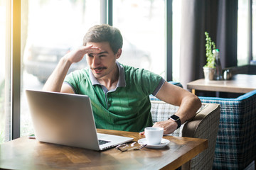 Young attentive businessman in green t-shirt sitting and working on laptop, holding hand on his forehead and looking to something. business and freelancing concept. indoor shot near window at daytime. Wall mural