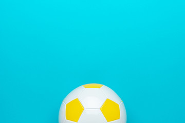 Top view of part of white and yellow soccer ball over turquoise blue background with copy space. Minimalist flat lay image of football ball as sport background.