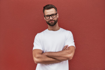 Wall Mural - Confident and stylish. Portrait of attractive bearded man in eyeglasses keeping arms crossed and looking at camera while standing against red wall outdoors