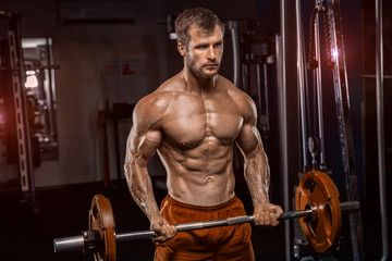 Keuken foto achterwand Fitness Shirtless tattooed man is lifting weight in sport club. He is standing and doing biceps curls. Male is training strength and relief of upper body