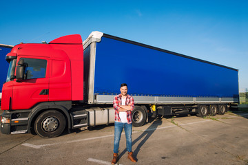 Portrait of professional American truck driver in casual clothing and boots standing in front of truck vehicle with long trailer. Transportation services. Wall mural