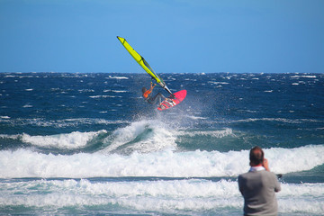 Selective focus on windsurfer jumping in the waves while a man is taking a photo of him