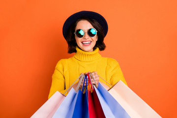 Photo of shopping cheerful girl wearing cap showing you what she has bought while isolated with orange background