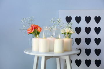 Beautiful burning candles with rose flowers on table