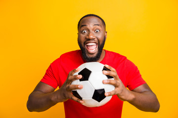 Photo of cute childish rejoicing american man ready to play football while isolated with yellow background Fototapete
