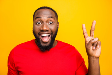 Close up photo of black man rejoicing enjoying showing you v-sign saying hi while isolated with yellow background Fototapete