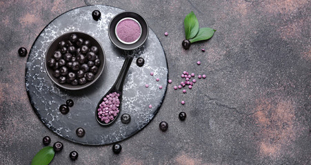 Fotobehang - Acai berries with powder and tablets on grey background
