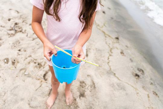 Girl Picking Up Plastic Straw on Beach
