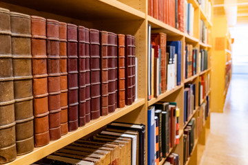 Antique leather cover books on wooden bookshelf with aisle perspective in university public...