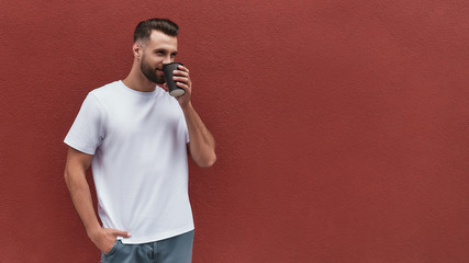 Wall Mural - Fresh coffee. Handsome man in casual clothes holding cup of coffee and looking aside while standing against red wall outdoors