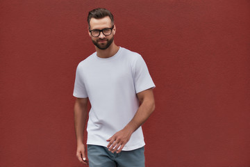 Wall Mural - Young and handsome. Portrait of attractive bearded man in eyeglasses smiling and looking at camera while standing against red wall outdoors
