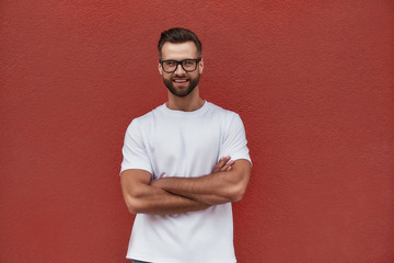 Wall Mural - Free day. Portrait of attractive bearded man in eyeglasses keeping arms crossed and looking at camera with smile while standing against red wall outdoors