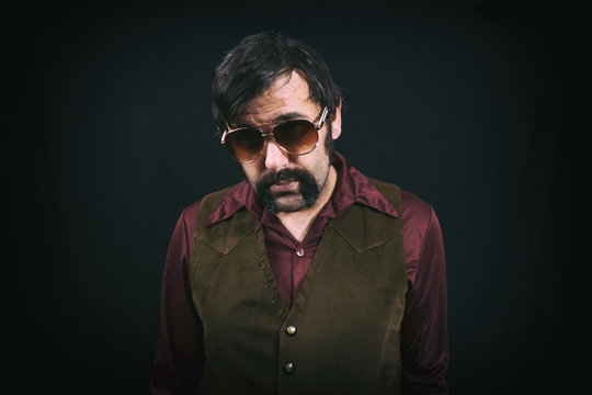 Man dressed in vintage 1970's era clothing, with big collars, mustache, a leather vest and sunglasses.