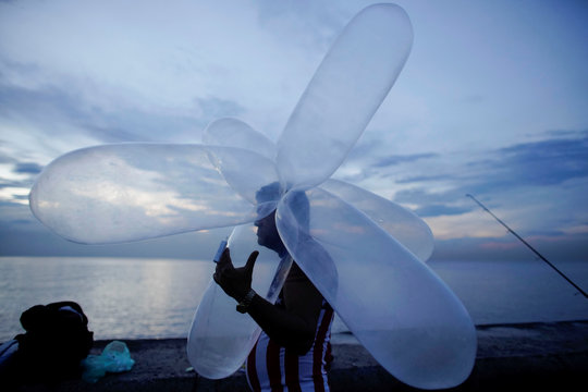Bus driver Carlos Torobu holds inflated condoms used for fishing at the seafront Malecon in Havana