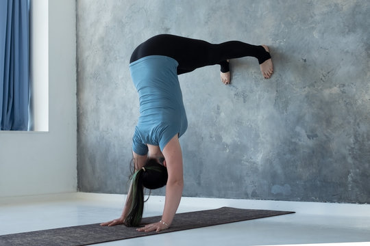 Woman learning to stand on hands near wall. Upside down yoga position. Studio shot