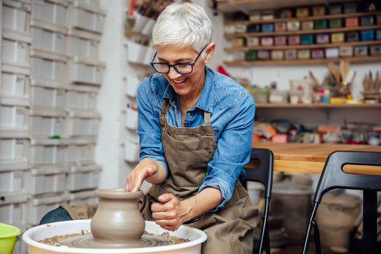 Senior female potter working on pottery wheel while sitting  in her workshop