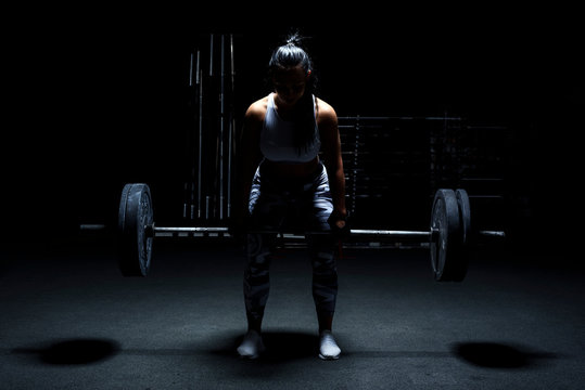 Female bodybuilder make her workout with weights - barbell. Light from above, dark background.