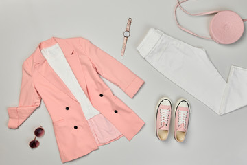 Fall fashion Flat lay. Trendy coral jacket, Stylish trousers, hipster sneakers. Creative autumn Woman Clothes Accessories layout. Fall Girl fashionable Outfit, autumnal pastel pink color.