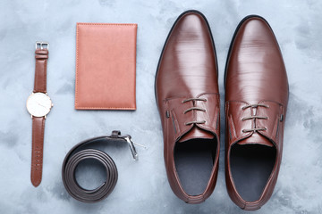 Male leather shoes with belt, passport and wrist watch on grey background