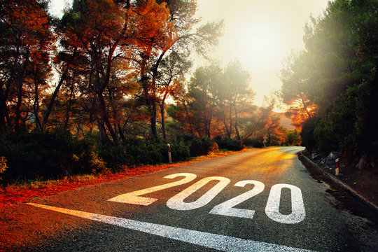 Conceptual entering new year 2020 on sunset asphalt road.