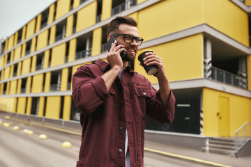 Wall Mural - Great news. Handsome young man in casual wear and eyeglasses drinking coffee and talking by phone with somebody while walking through the city street
