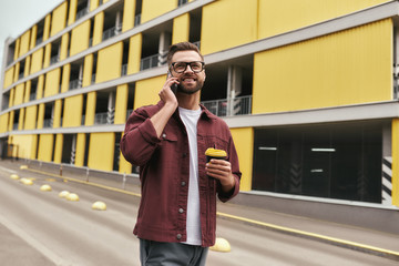 Wall Mural - Happy to hear you. Handsome young man in casual wear and eyeglasses holding a disposable cup and talking by phone with somebody while walking through the city street