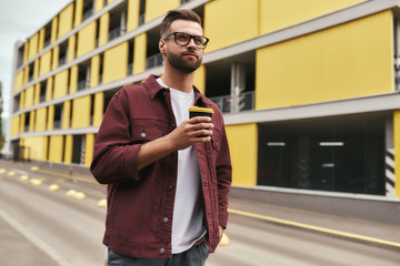 Wall Mural - I love my city. Handsome bearded man in casual wear and eyeglasses holding a disposable cup while walking through the city street