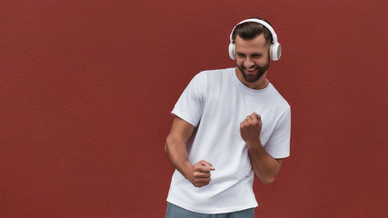 Wall Mural - Good mood Portrait of happy handsome man in headphones listening to the music and dancing against red wall outdoors