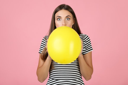 Young woman blowing yellow balloon on pink background