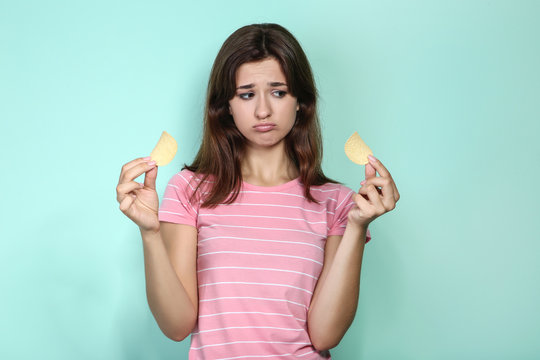 Young woman with potato chips on mint background