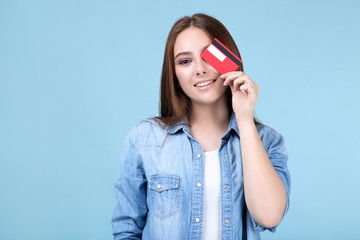 Young woman holding credit card on blue background