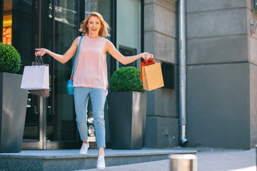 Joyful lady walking out of the shop with purchases stock photo