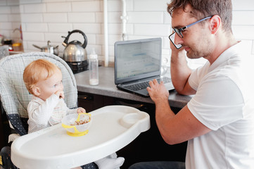 Happy young father working at home and sitting with a baby girl. Father feeding a baby during talking the mobile phone