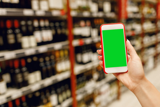 Girl in the supermarket using a mobile phone choosing alcoholic drinks.