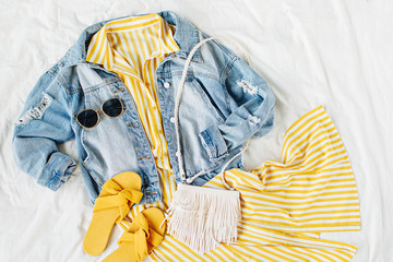 Wall Mural - Blue jean jacket and Yellow dress  with  bag and  slippers on white bed. Women's stylish autumn or spring outfit. Trendy clothes. Fashion concept.  Flat lay, top view.