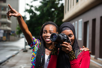 young women with camera, smiling.