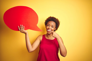 Young african american woman holding speech bubble over yellow isolated background very happy pointing with hand and finger Fototapete