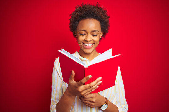 African american woman reading a book over red isolated background with a happy face standing and smiling with a confident smile showing teeth