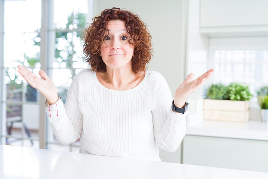 Beautiful senior woman wearing white sweater at home clueless and confused expression with arms and hands raised. Doubt concept.