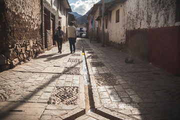 two persons walking in the street. A vision of a central old chanel of water in the floor. Pisac,...