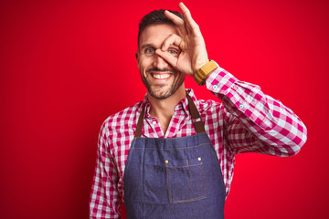 Young handsome man wearing shop owner apron uniform over red isolated background doing ok gesture with hand smiling, eye looking through fingers with happy face.