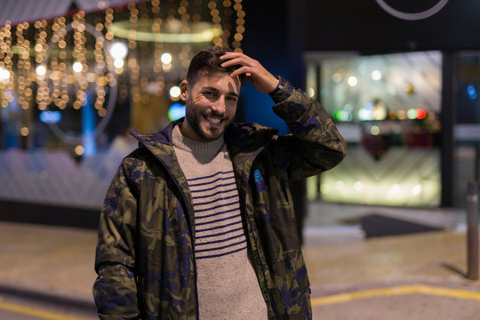 Young handsome man possing and smiling. Street style at night