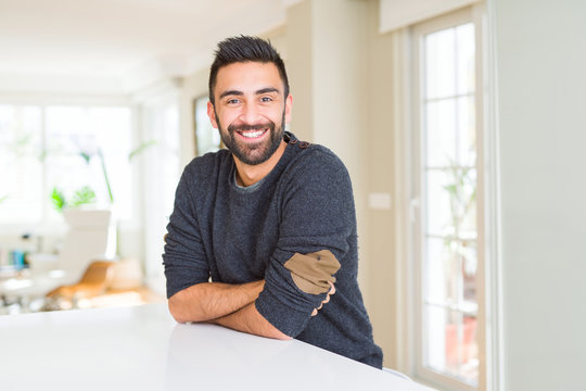 Handsome hispanic man wearing casual sweater at home happy face smiling with crossed arms looking at the camera. Positive person.