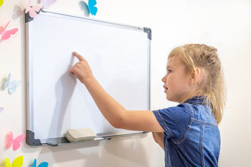 Little girl showing something on whiteboard, education and back to school concept with copy space