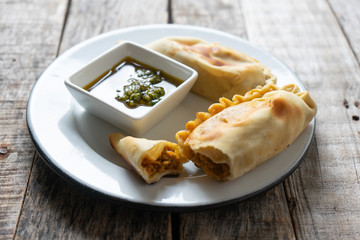 Argentine empanadas with chimichurri sauce on wooden background Wall mural