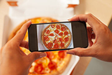 Taking photo of pizza dinner with mobile phone.